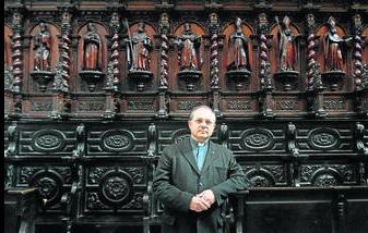 El deán de la Catedral, Guillermo Domínguez Leonsegui, apoyado en uno de la sillería del coro del primer templo