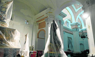 El interior de la iglesia de la Castrense, con las imágenes y altares cubiertos por plásticos por la pintura que recientemente se realizó de todo el templo.